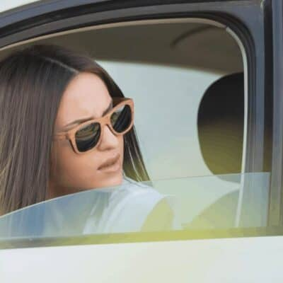 Giving Grace to Others - Extending Grace - A woman with sunglasses looking back outside the driver's side window of a car, looking annoyed.