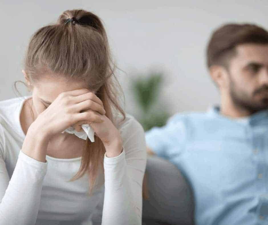Strife in Marriage - Marital Strife - A couple on a couch clearly arguing with the woman with her head in her hands holding a tissue