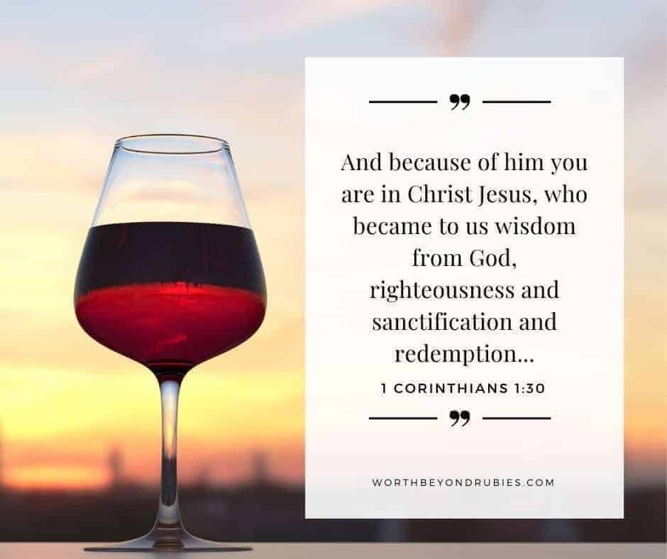 A cup of wine on a table with the sunset in the background with 1 Corinthians 1:30 on the image