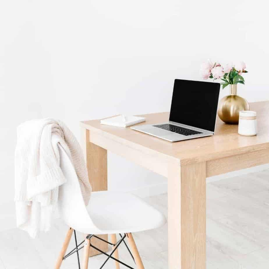 An image of a laptop on a wooden table with a plant behind it and a chair with a sweater tossed over the back in front of the table