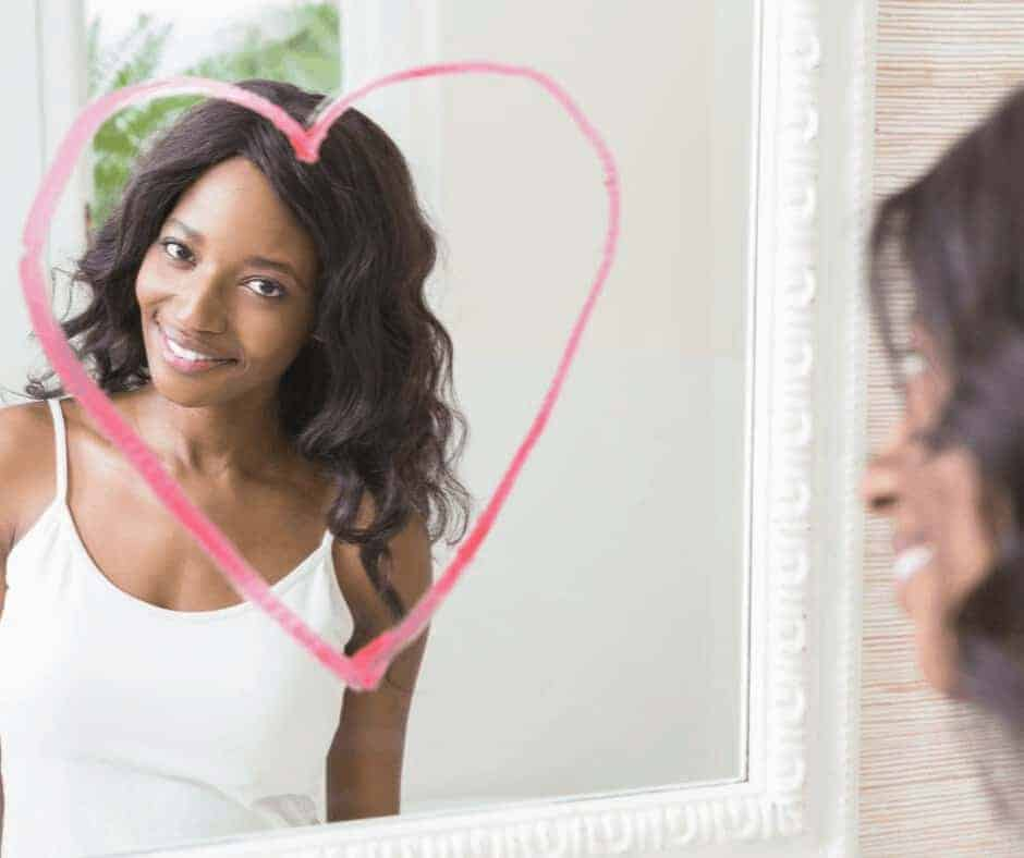 What the Bible Says About Body Image - A beautiful black woman looking into a mirror smiling with a heart drawn in lipstick around her image