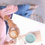 Unmet Expectations - A Simple Life Lesson From a Cup of Coffee - A woman in pink sitting at a bistro table with a cup of coffee