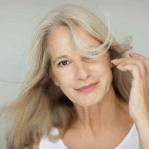 An image of a beautiful, middle aged woman with long blondish-gray hair