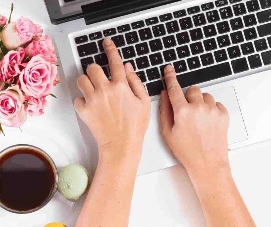 Christian Woman Blogger - A woman's hands typing on a laptop with coffee next to her and flowers on the desk