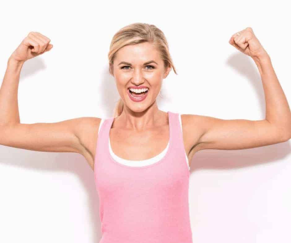 Work Out Your Faith - Spiritual Growth- Building Spiritual Muscles - A blonde woman in a pink tank top with her arms up making muscles