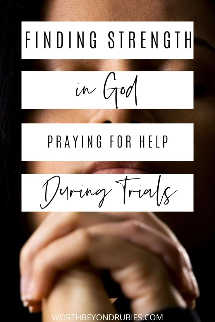 A dark lit image of a woman of Hispanic heritage with her eyes closed and her hands folded in prayer in front of her with text that says Finding Strength in God - Praying for Help During Trials