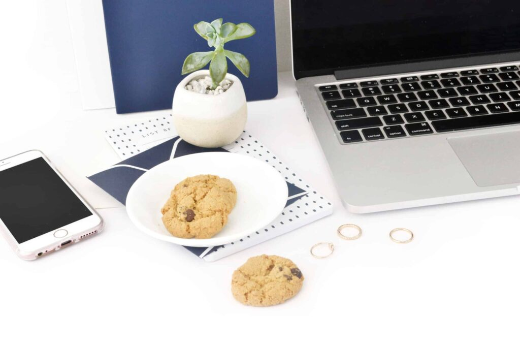 An image of a laptop on a desk with cookies on a plate next to it with one sitting on the desk and a succulent and blue accessories in the background