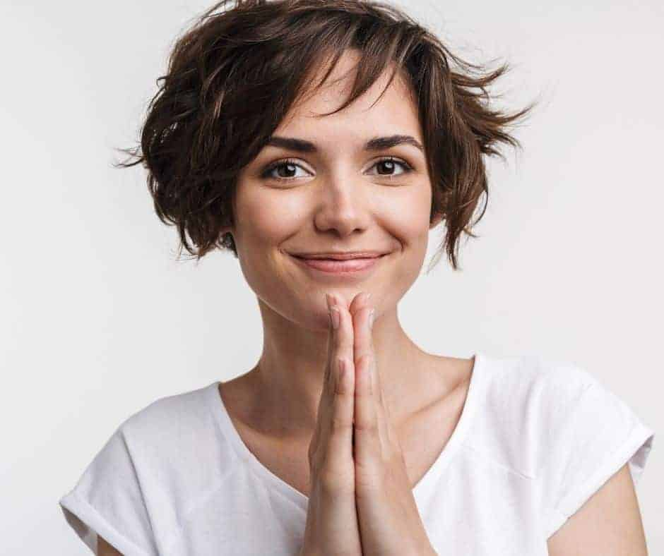 A woman with short brown hair in a white t-shirt with her hands up in prayer smiling and a text overlay that says What is Spiritual Warfare - Spiritual Warfare Bible Study