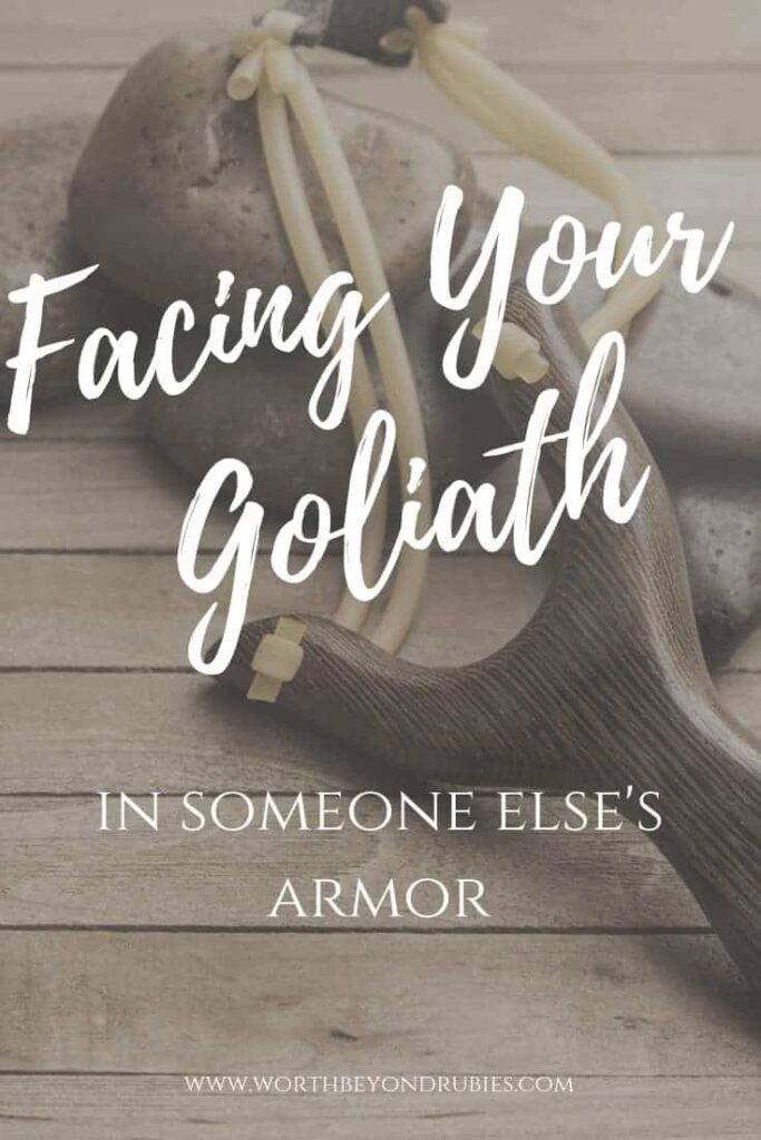 A wooden backdrop with stones and a slingshot with a text overlay that says Facing Your Goliath in Someone Else's Armor