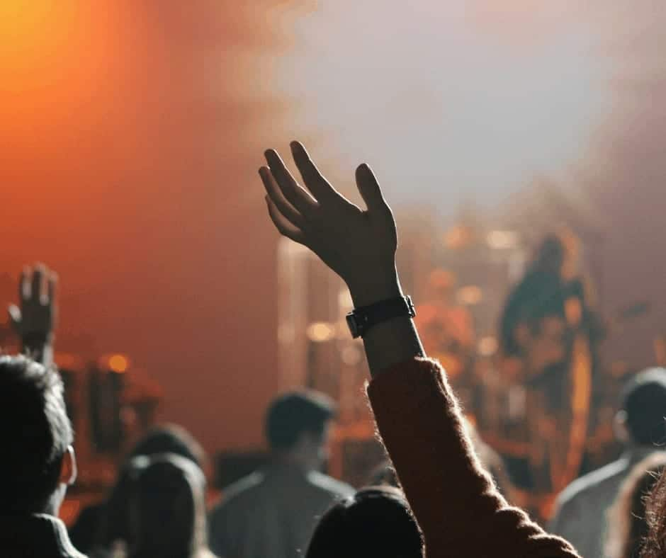 Jesus Fan or Follower? - A woman at a Christian concert with her hand raised