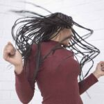 An image of a black woman with long hair dancing and whipping her hair around