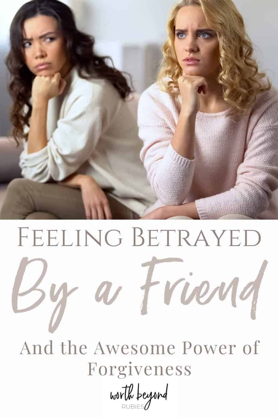 An image of a blonde woman and a brunette woman sitting next to each other on a couch and both have a hand to their chin looking angry like they are arguing or mad at eachother. The blonde is looking away and the brunette is looking at the blonde. There is a text headline under the image that says Feeling Betrayed by a Friend - And the Awesome Power of Forgiveness