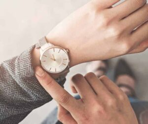 What Does it Mean to Wait for the Lord? A woman's arm with a watch and she is pointing at it as though waiting for someone or something