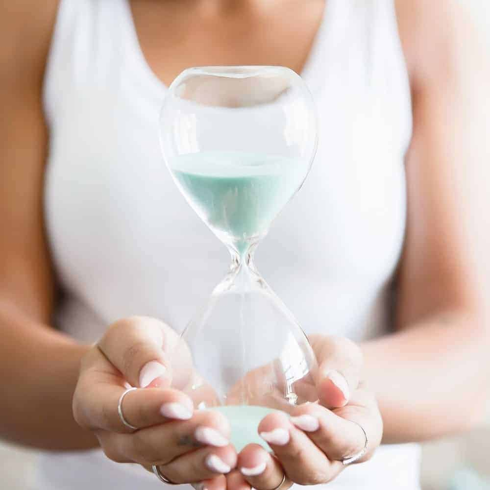 An image of a woman in a white sleeveless top holding an hourglass with light blue sand in it