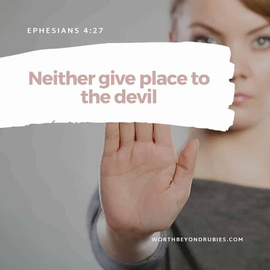 "Signs of Spiritual Warfare - a woman with her hand in front of her in ""stop"" movement with Ephesians 4:27 in text overlay"