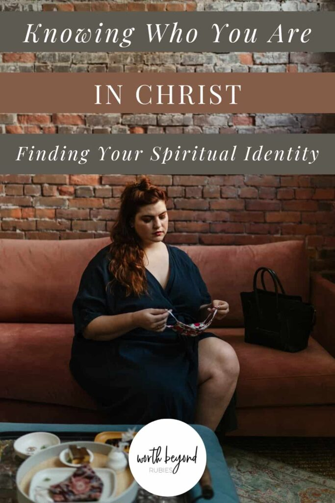 A woman with long red hair sitting on a rust colored couch against a red brick wall and she is holding what looks like a necklace in her hand and she is looking down at it almost sadly and a text overlay that says Knowing Who You Are in Christ - Finding Your Spiritual Identity