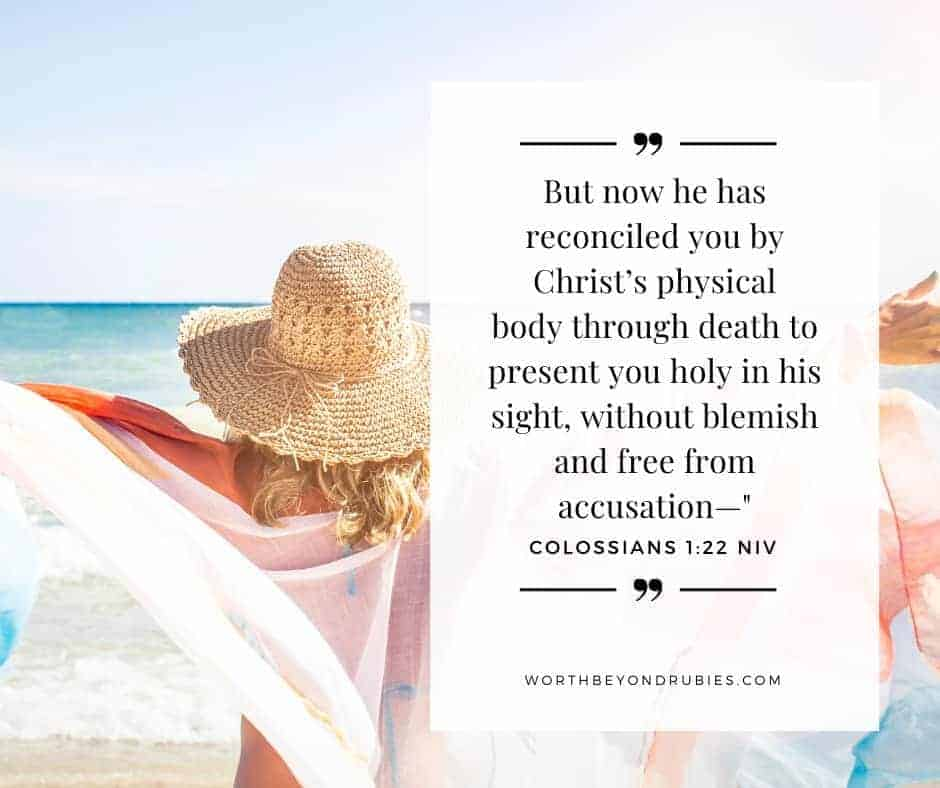 A woman on a beach with a wrap spread over her outstretched arms and Colossians 1:22 quoted