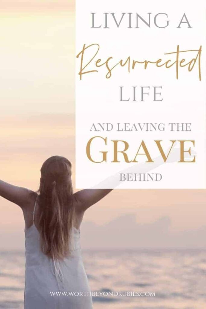 Living a Resurrected Life - Leaving the Grave Behind - A woman standing on the beach at sunset with her arms stretched up toward heaven