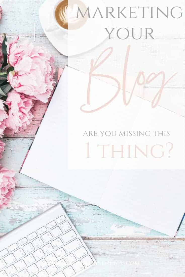 Marketing Your Blog - Christian blogger - A pretty white wooden backdrop with pink flowers to the left and a white computer keyboard in the lower left and a notebook opened to a blank page in the middle