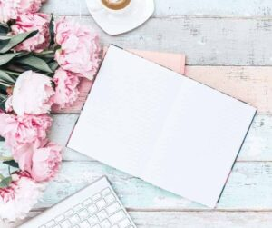 Marketing Your Blog - A pretty white wooden backdrop with pink flowers to the left and a white computer keyboard in the lower left and a notebook opened to a blank page in the middle