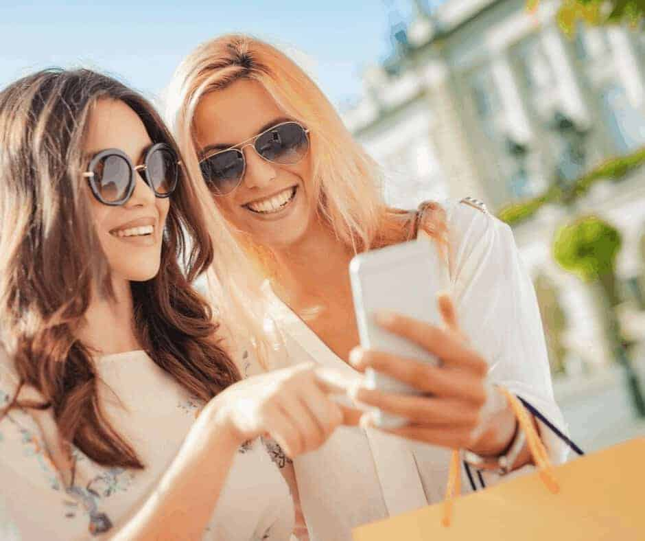 The Comparison Trap - What Does The Bible Say About Comparing Yourself to Others? - Two Woman with sunglasses on and shopping bags on their arms looking at a cell phone and pointing at it smiling