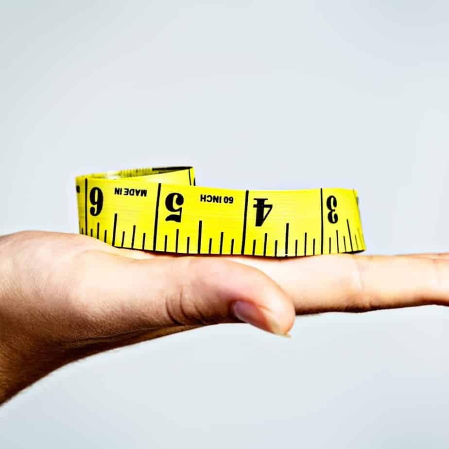 An image of a hand held flat with a yellow measuring tape sitting on top of it