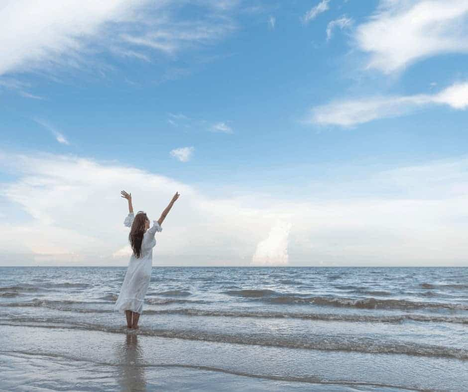 Job's Faith - My Redeemer Lives - A study of Job - a woman with arms raised standing on the shore in front of the ocean