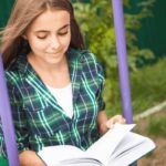 Best Teen Bibles for Teenage girls - an image of a teen girl sitting on a swing in a green plaid shirt reading a Bible