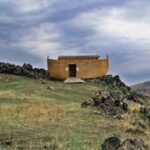 An image of Noah's ark resting on the ground on a hill with a cloudy sky over head
