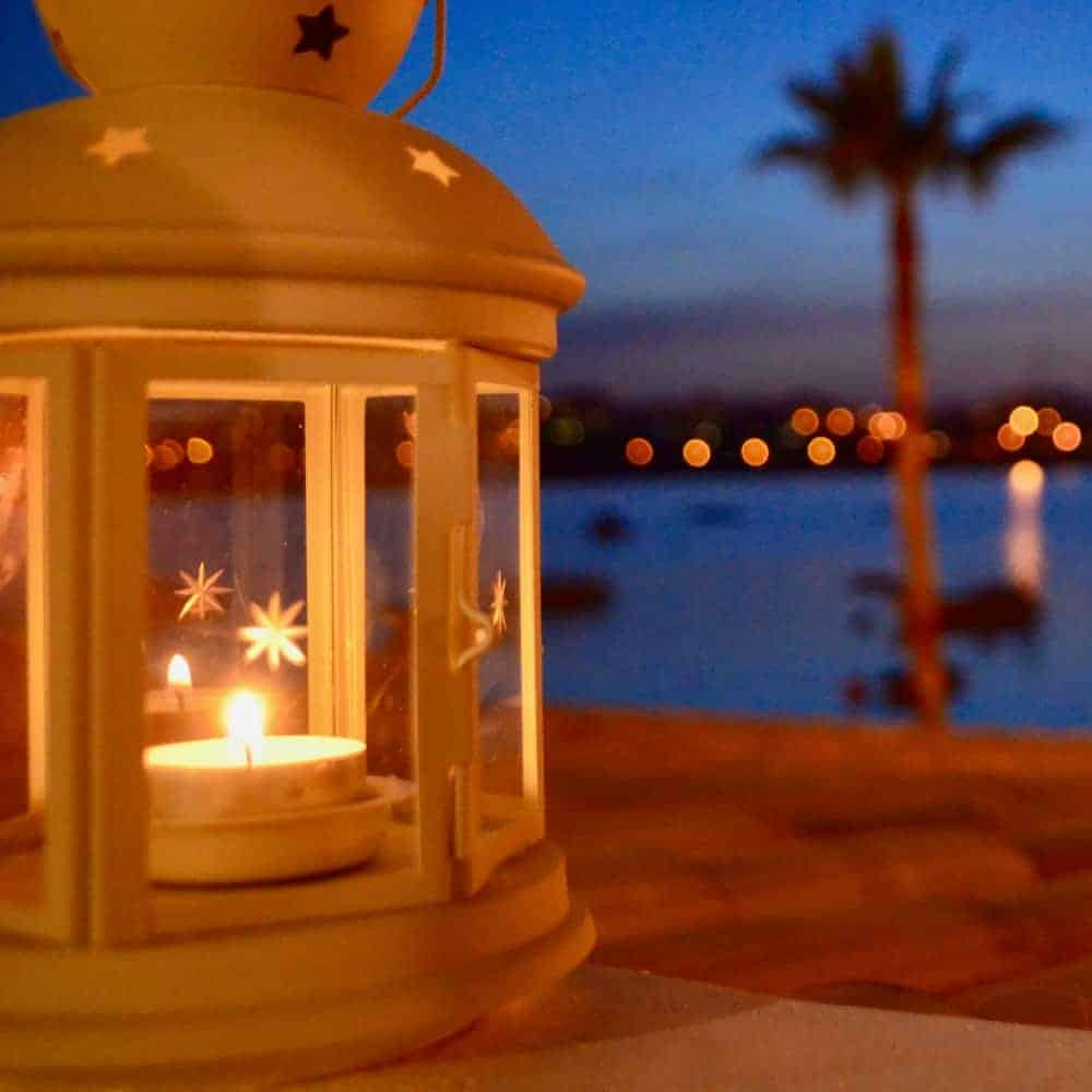 an image of a lantern on a table near the water