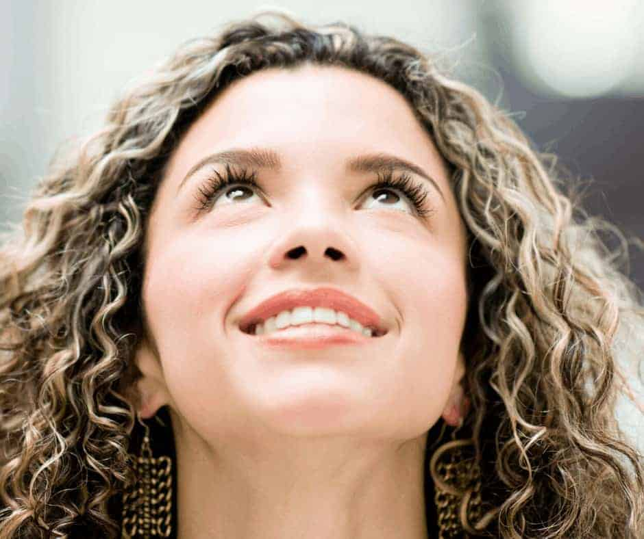 Keep Your Eyes on Jesus in the Midst of the Storm - A woman with long curly hair looking upward