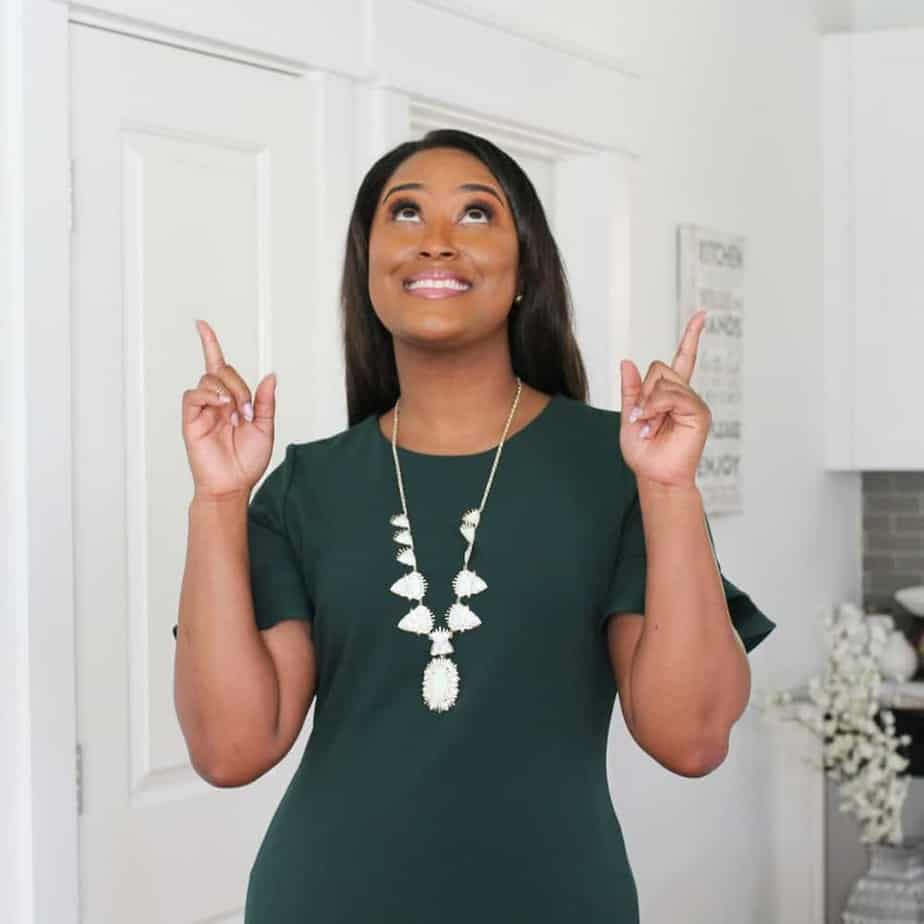 An image of a black woman with long hair and in a green dress standing in a kitchen looking up and pointing with her two index fingers