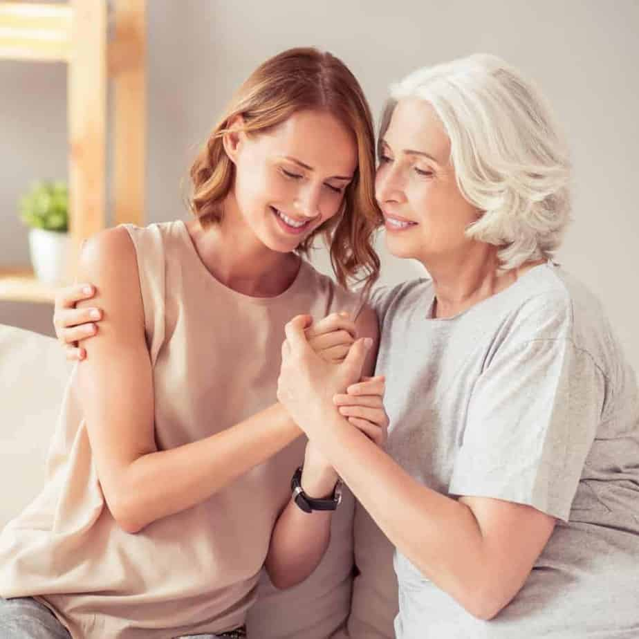 An image of a woman sitting on a couch next to her mother holding hands and both smiling