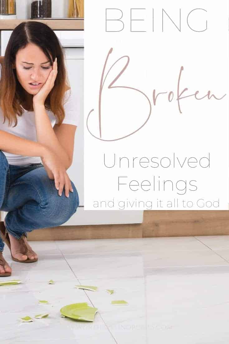 A woman squatting down on the floor looking at a broken plate with a text overlay that says 'Being Broken - Unresolved Feelings and Giving it All to God'