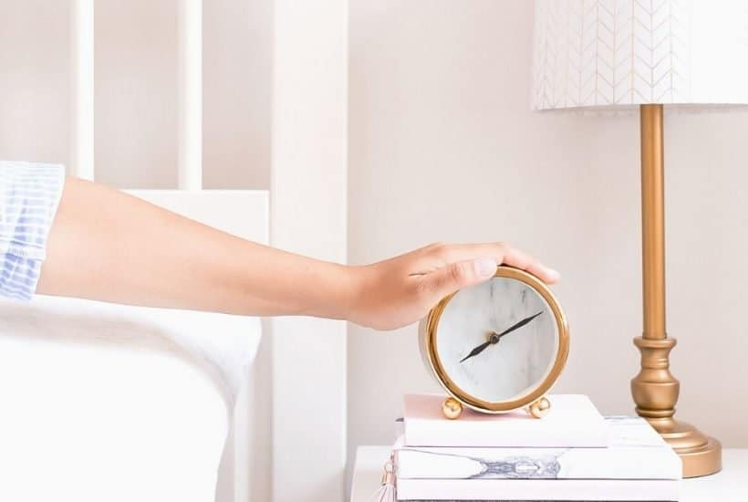 A woman's arm reaching out from bed to touch an alarm clock