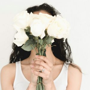 A woman in a white tank top holding white flowers up in front of her face