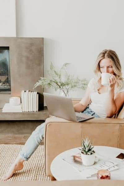 A woman sipping coffee while looking at her tablet