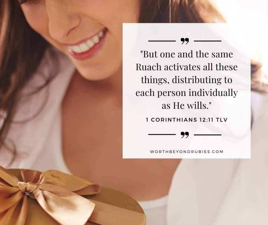 An image of a woman looking down at a gift wrapped in gold and 1 Corinthians 12:11 quoted from the Tree of Life Version