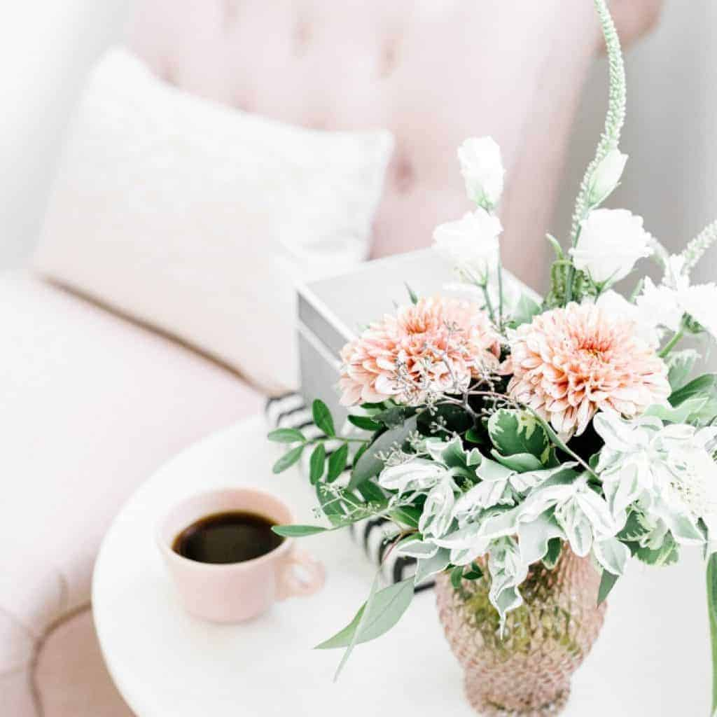 About Worth Beyond Rubies - an image of a lounge seat with a table with flowers and a cup of coffee next to it
