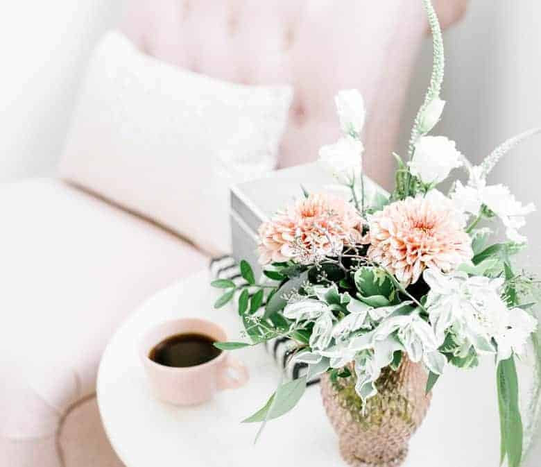 An image of a setee with a white pillow on it and a round table with flowers in a vase and a cup of coffee -  About Worth Beyond Rubies