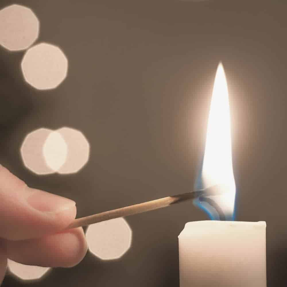 An image of a woman's hand holding a match and lighting a candle with glimmering lights in the background