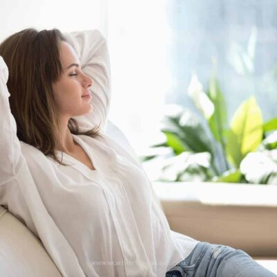 """A woman leaning back and resting on a couch with a text overlay that says """"Keeping the Sabbath - 11 Ways to Keep the Sabbath Holy"""""""