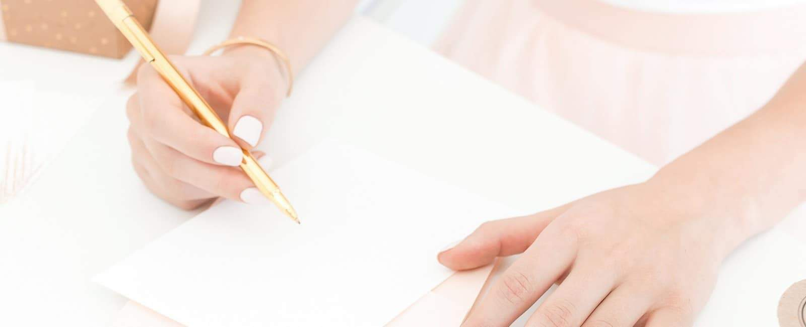 A woman in peach writing on paper with a gold pen
