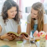 two teenage girls sitting together at a table, smiling and looking at a Bible