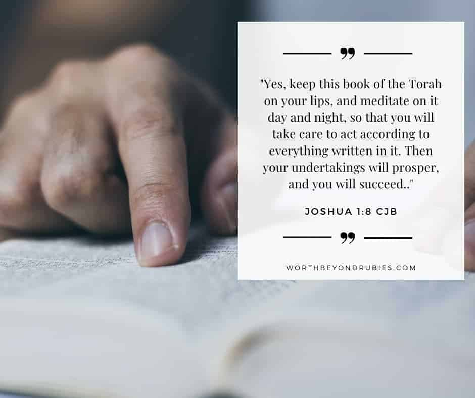 Man's hand touching page in Bible with Joshua 1:8 quoted from the Complete Jewish Bible