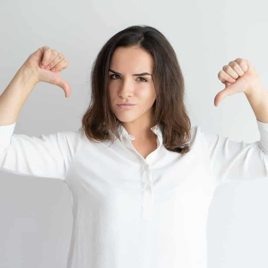 An image of a brunette woman in a white shirt with her thumbs pointing at herself - The Spirit of Pride