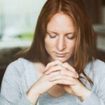 An image of a red-headed woman in a gray shirt sitting at a table with her hands folded in prayer and text that says The Power of Prayer - Intentional Prayer or Kavanah