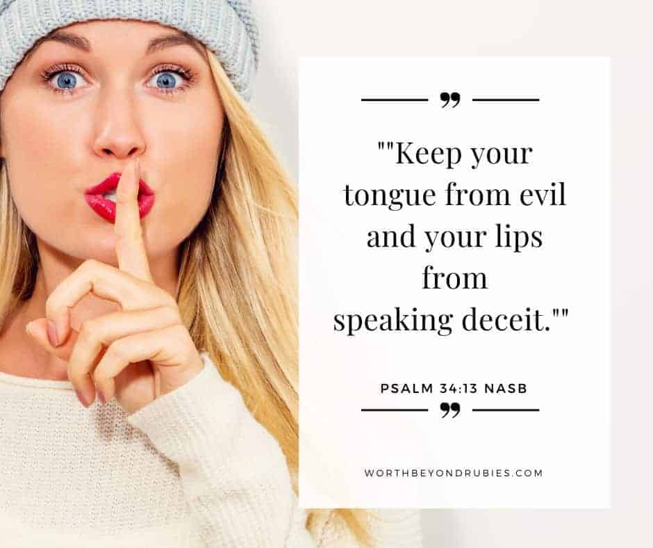 A woman with long blonde hair, red lips and a grey knit hat on with her finger up to her lips in a shh motion - What Does the Bible Say About Gossip?