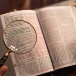 An image of a magnifying glass being held over an open Bible and text that says Did God REALLY Say That? - Questioning What God Says