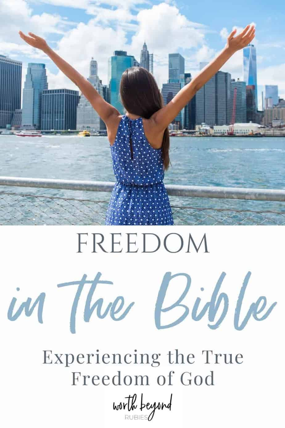 An image of a woman standing on the river facing the New York City skyline and she is wearing a blue, polka dot dress and her arms are up in the air toward the sky - a text overlay that says Freedom in the Bible - Experiencing the True Freedom of God